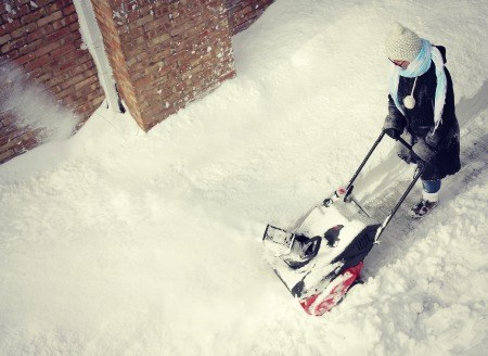 Women using a snow blower.
